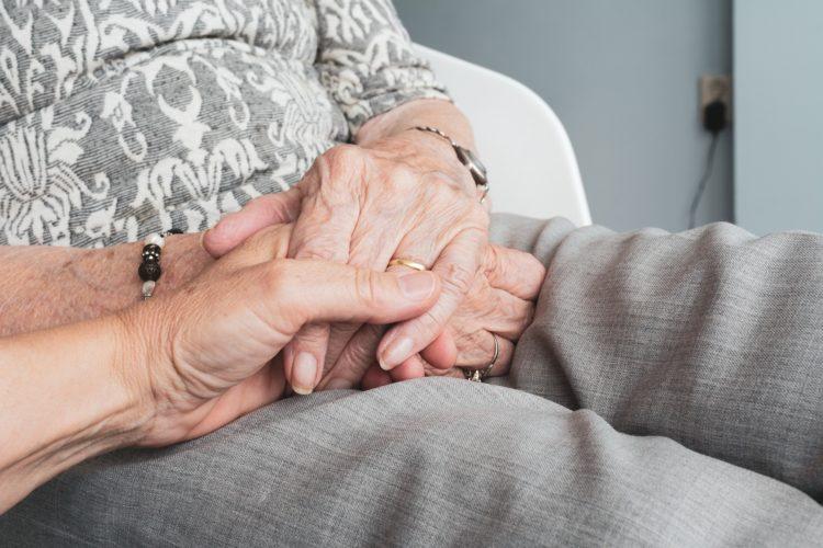 Vanhuksen ja hoitajan kädet.