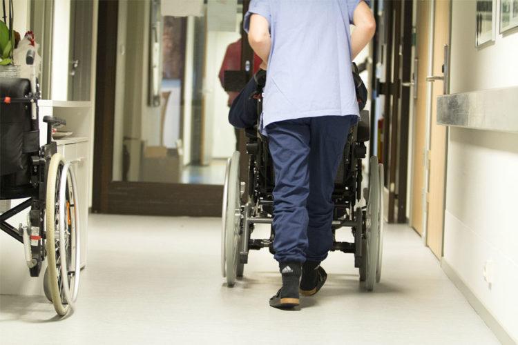 Hoitaja työntää potilasta pyörätuolilla
